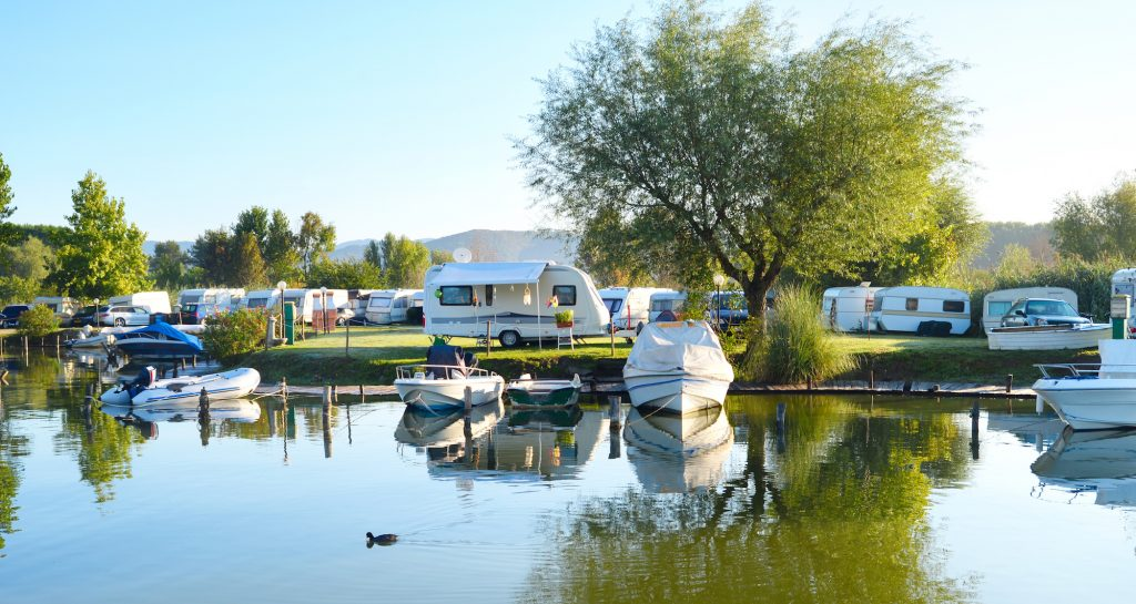 Camping site and community on a lake with rvs and boats