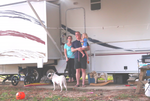 rv family in front of vehicle with girl and dog